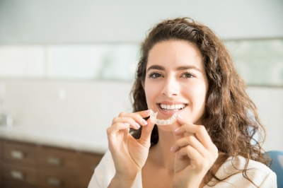 Young woman smiling and holding her Invisalign clear aligners