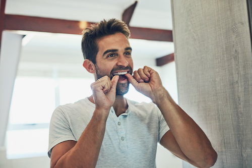 adult man flossing in front of a mirror
